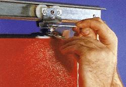 Die Distanz zwischen den Laufrollen und dem Türblatt kann durch die Stellschrauben verändert werden. Danach die Kontermutter anziehen.