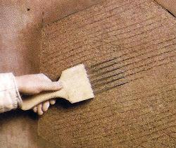 Die Fläche wird mit einem Kratzer aufgebrochen, um eine kraftschlüssige Verbindung zwischen den Mörtellagen zu ermöglichen.