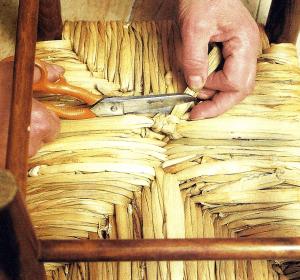 Den Abschluss der Arbeit mit Binsen Halmen bildet ein besonders sorgfältig ausgeführter Knoten, der die Enden des letzten Halm Paars sichert.